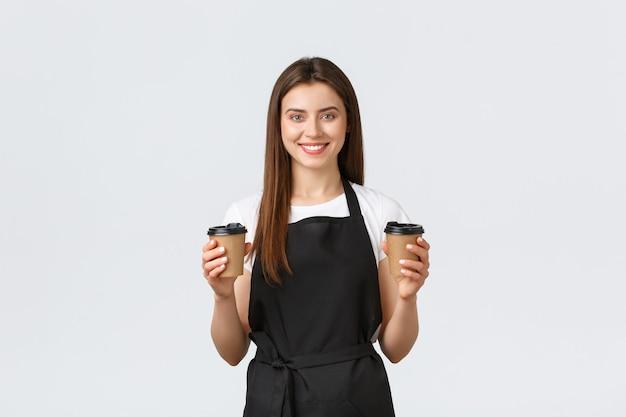 Medewerkers van supermarkten, kleine bedrijven en coffeeshops concept. vriendelijk lachende barista in zwarte schort met drankje. vrolijke cafémedewerker die twee papieren bekers vasthoudt om afhaalmaaltijden te geven