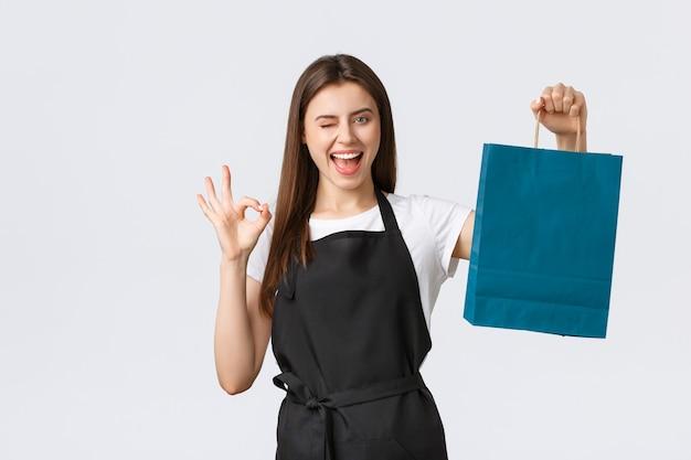 Medewerkers van supermarkten, kleine bedrijven en coffeeshops concept. vriendelijk lachende mooie kassier in zwarte schort die papieren zak overhandigt met je cadeau-aankoop, goed teken laat zien en brutaal knipoogt