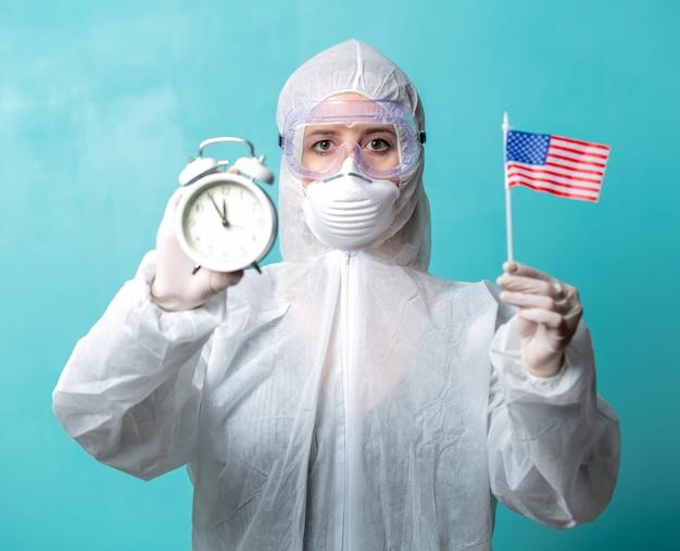 Medic in beschermende kleding houdt de amerikaanse vlag vast en de alarmklok vraagt je om thuis te blijven