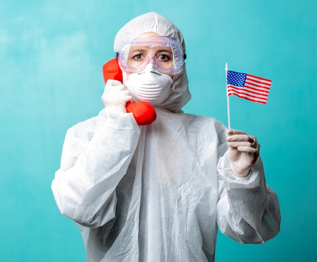 Medic in beschermende kleding houdt rode handset 911 en de vlag van de vs.