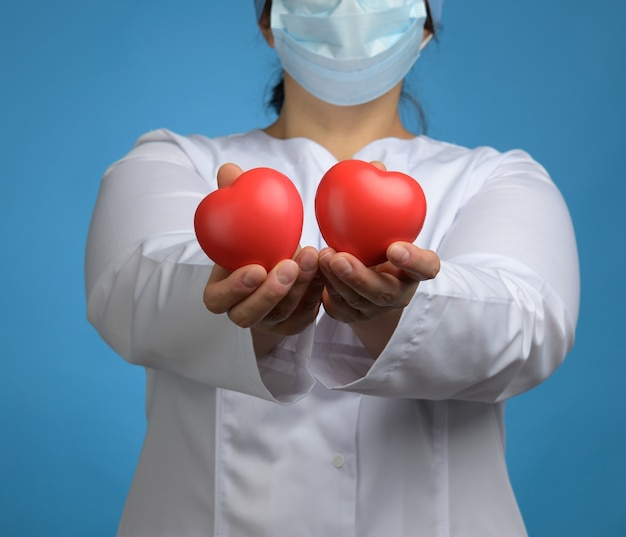 Medic in een witte jas, een masker staat en houdt een rood hart op een blauwe achtergrond, het concept van donatie en vriendelijkheid