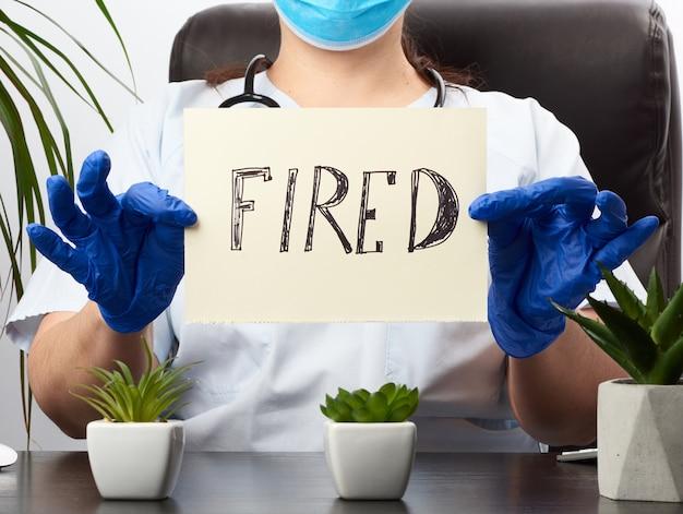 Medic in een witte jas met een vel papier met de inscriptie in brand gestoken