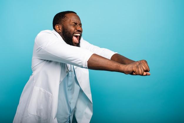 Medic is blij en danst. vrolijke uitdrukking. blauwe achtergrond
