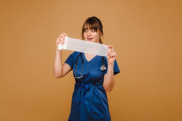 Medic vrouw in witte jas en masker houdt een gedraaid gaasverband voor het aankleden van wonden, witte achtergrond.