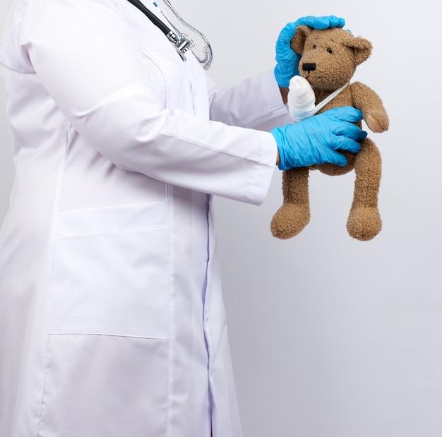 Medic vrouw in witte jas met knopen met een bruine teddybeer met een wit gaasverband vastgebonden met haar poot,