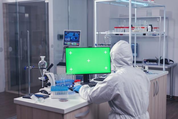 Medica-personeel met behulp van computer met groene mok omhoog in wetenschappelijk laboratorium. team van microbiologen die vaccinonderzoek doen en schrijven op apparaat met chroma key, geïsoleerd, mockup-display.