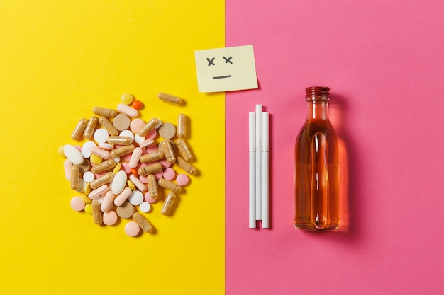 Medicatie kleurrijke tabletten pillen gerangschikt abstract, fles alcohol, sigaretten op geel roze roze kleur achtergrond. papieren sticker verdrietig glimlach gezicht. behandeling, keuze gezonde levensstijl. ruimte kopiëren.