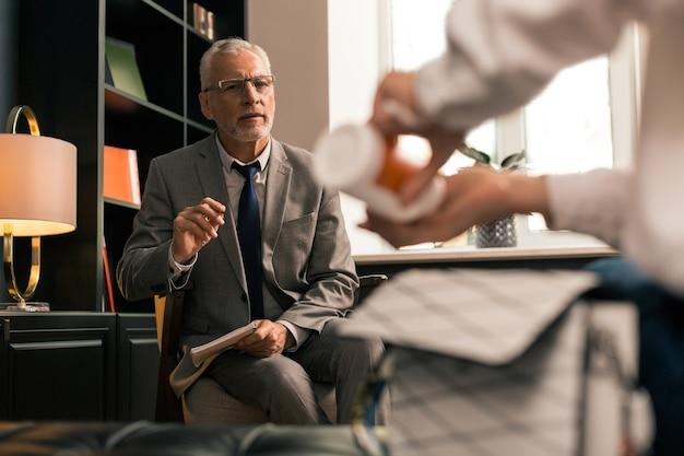 Medicatie nemen. senior psycholoog zittend in een stoel terwijl hij nauwlettend toekijkt hoe zijn vrouwelijke patiënt antidepressiva slikt in zijn aanwezigheid