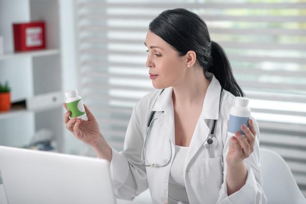 Medicatie, online consult. donkerharige volwassen vrouw in een witte jas met een medicijn in haar handen, zittend op een werkplek met een laptop, in een goed humeur.