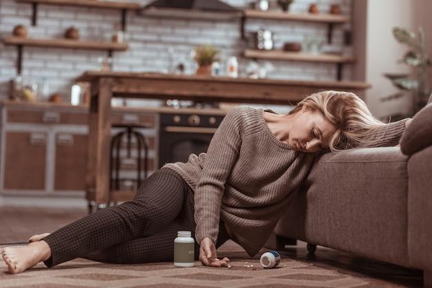 Medicatie vergiftiging. rijpe blonde vrouw valt op de vloer in de buurt van de bank na medicatievergiftiging