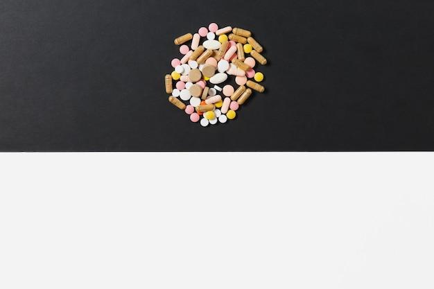 Medicatie witte kleurrijke ronde tabletten gerangschikt abstract op witte zwarte achtergrond