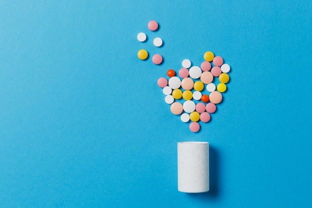 Medicatie witte, kleurrijke ronde tabletten in de vorm van een hart geïsoleerd op een blauwe achtergrond. pillen geometrische vorm, fles. concept van gezondheid, behandeling, keuze, gezonde levensstijl. ruimte advertentie kopiëren.
