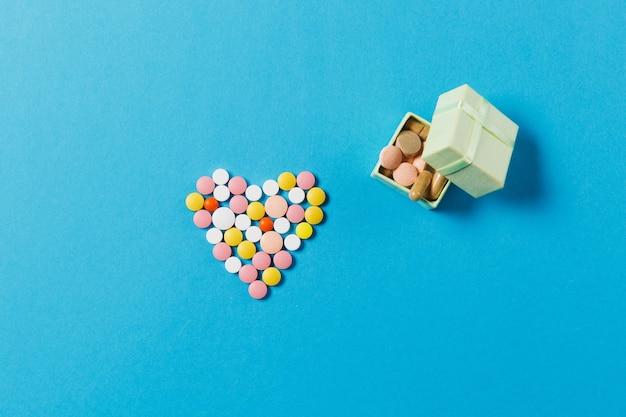 Medicatie witte, kleurrijke ronde tabletten in de vorm van een hart geïsoleerd op een blauwe achtergrond