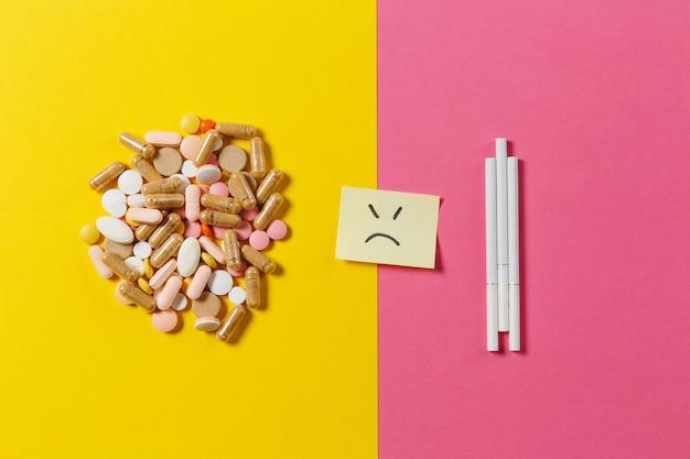 Medicatie witte kleurrijke ronde tabletten pillen gerangschikt abstracte drie sigaretten op gele kleur achtergrond