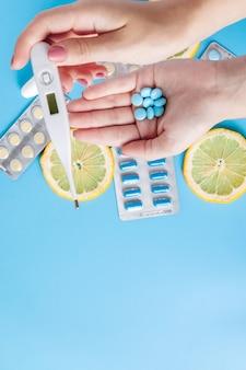 Medicijnen, pillen, thermometer, traditionele geneeskunde voor de behandeling van verkoudheid, griep, hitte op een blauw