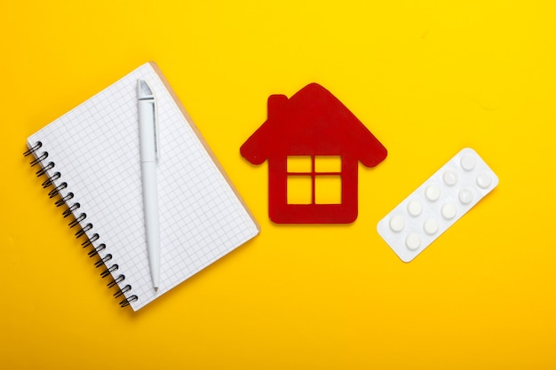 Medicijnen thuis. thuisbehandeling. huisbeeldje, blisterverpakking van pillen, notitieboekje op gele achtergrond. bovenaanzicht