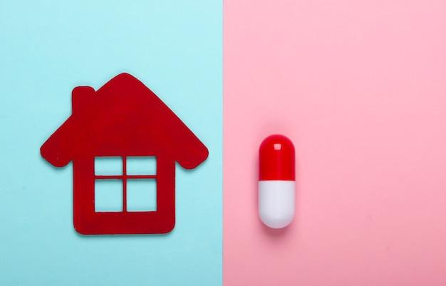 Medicijnen thuis. thuisbehandeling. huisbeeldje, pil op een blauw-roze pastel achtergrond. bovenaanzicht