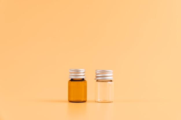 Medicijnfles geplaatst, blanco etiketpakket voor mockup op de oranje achtergrond. het concept van natuurlijke schoonheidsproducten.
