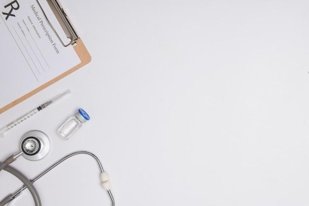 Medicijnflesje met coronavirusvaccin covid-19. medische glazen flacon, stethoscoop en spuit voor vaccinatie. vloeibaar vaccin in geïsoleerd laboratorium, ziekenhuis of apotheekconcept.