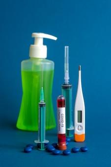 Medicijntablet, thermometer, fles met ontsmettingsmiddel en spuit of injectie met een reageerbuis met een bloedmonster om te testen op de aanwezigheid van coronavirus
