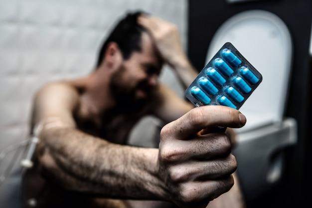Medicijnverslaving. de jonge mens zit op vloer in toilet en houdt plaat van blauwe pillen. hand is omwikkeld met vlecht voor het nemen van drugs.