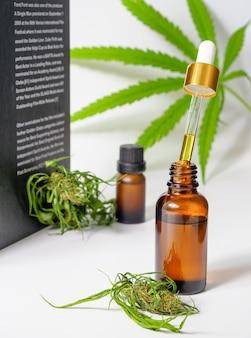 Medicinale cbd-hennepolie-extracten. cannabis blad bloem en boek op witte ondergrond, medisch onderzoek concept