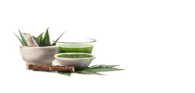 Medicinale neem bladeren in een mortier en een stamper met neem pasta, sap en takjes op een witte ondergrond