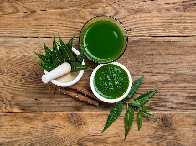 Medicinale neem bladeren in een vijzel en stamper met neem pasta, sap en takjes op houten oppervlak