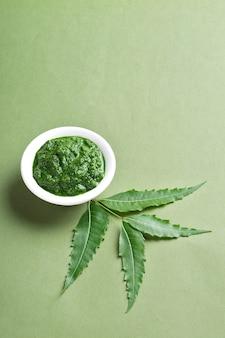 Medicinale neem bladeren met pasta in kom op groen oppervlak