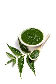 Medicinale neembladeren met neempasta in lepel en bord op wit oppervlak (azadirachta indica)