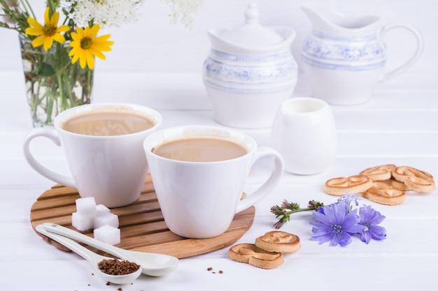 Medicinale planten cichorei, dieet drinken cichorei in een beker met melk voor het ontbijt op een witte tafel.