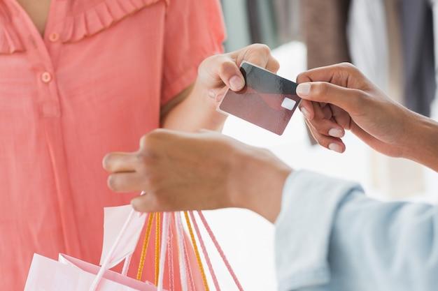 Medio gedeelte van klant die het winkelen zakken en creditcard van verkoopster ontvangt