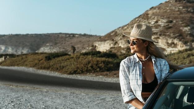 Medio geschoten blonde vrouw die zich uit autoraam op strand bevindt