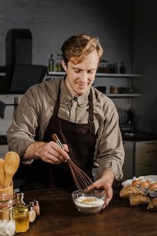 Medio geschoten chef-kok die ingrediënten zwaait
