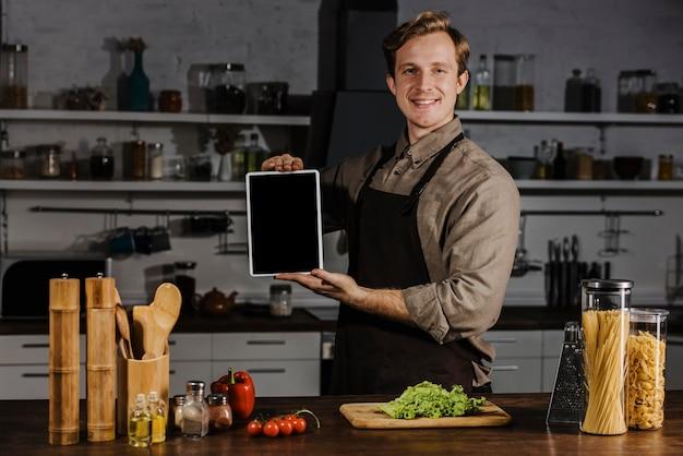 Medio geschoten chef-kok die lege tablet toont