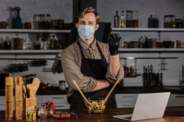 Medio geschoten chef-kok die met masker saladeingrediënten mengen dichtbij laptop