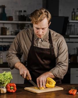 Medio geschoten chef-kok die paprika snijdt