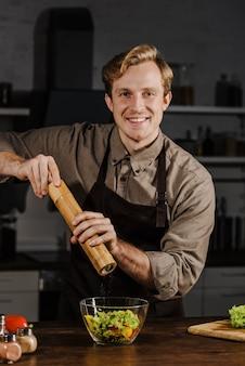 Medio geschoten chef-kok die peper aan salade toevoegt