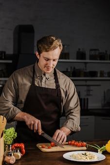 Medio geschoten chef-kok die tomaten snijdt
