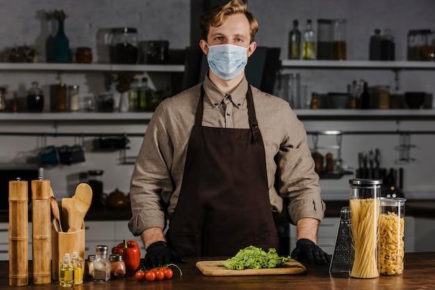 Medio geschoten chef-kok met masker en salade