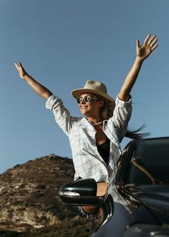 Medio geschoten gelukkige blonde vrouw die zich uit autoraam op strand bevindt