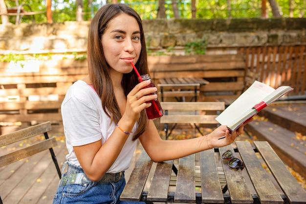 Medio geschoten meisje met boek en vers sapfles