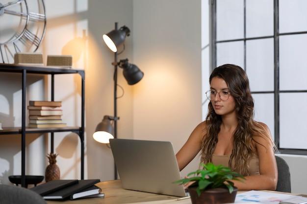 Medio geschoten vrouw die laptop bekijkt