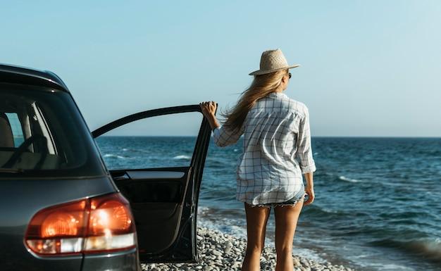 Medio geschoten vrouw die met de auto naar zee kijkt