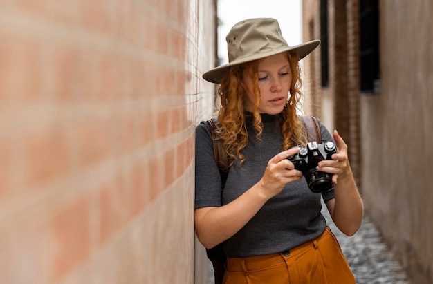 Medio geschoten vrouw die met hoed camera bekijkt
