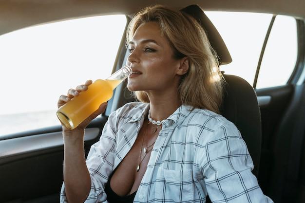 Medio geschoten vrouw die sap in auto drinkt