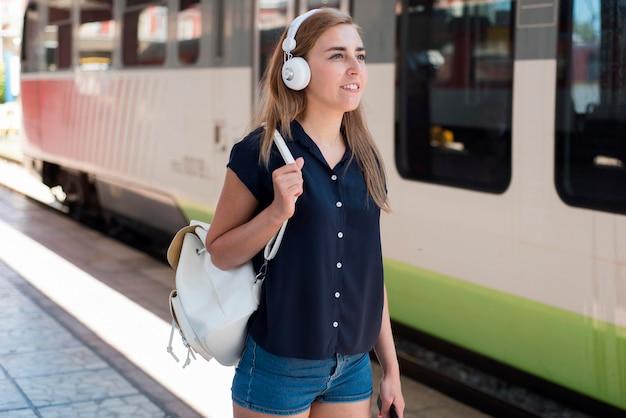 Medio geschoten vrouw met hoofdtelefoons in treinstation