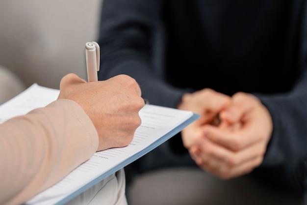 Medio geschoten vrouwentherapeut die aantekeningen op klembord maakt
