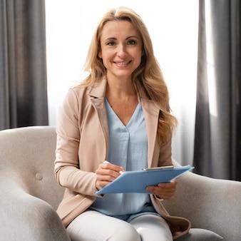 Medio geschoten vrouwentherapeut met klembord