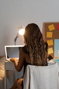 Medio geschoten vrouwenzitting bij bureau met laptop